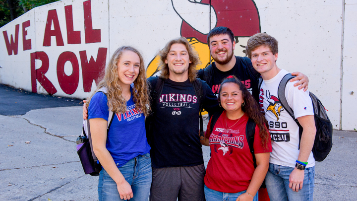 "VCSU students smiling for a photo by the ""We All Row"" wall"